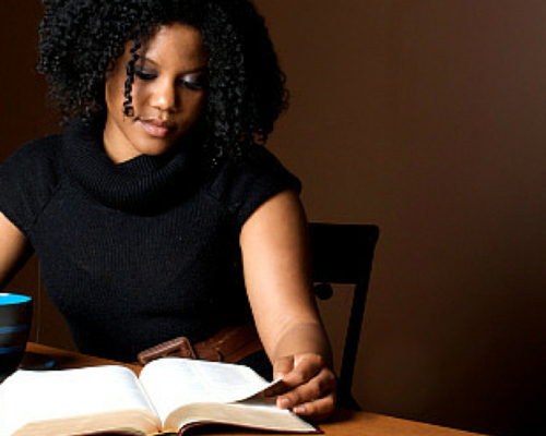 Black Woman curly hair reading